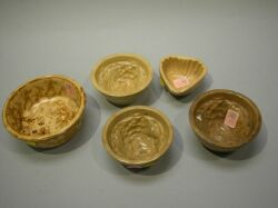 Four Small Yellowware Pudding Molds and a Rockingham Glaze Bowl.