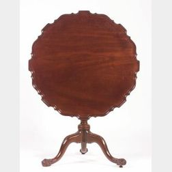 George III Mahogany Tilt-top Tripod Table, 18th century, with pie crust top above a spiral fluted stem on carved cabriole legs ending i