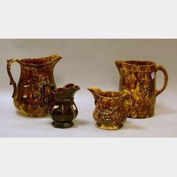 Two Bennington-type Glazed Stoneware Pitchers and Two Milk Jugs.