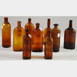 Nine Assorted Amber Pressed Glass Bottles