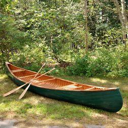 Arthur E. Levenseller 20-foot Canoe with Two Canoe Paddles.     Estimate $1,000-1,500