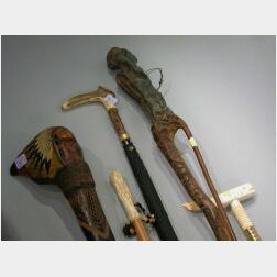 Collection of Five Carved Wood, Ivory, and Antler Clubs, Canes, and an Umbrella.