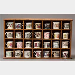 Collection of Transfer-decorated Alphabet Children's Mugs in a Pine Cupboard
