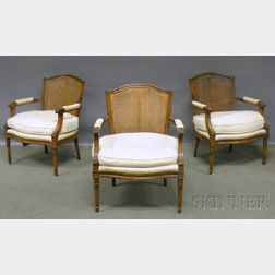 Set of Three Louis XVI-style Upholstered and Caned Carved Walnut Fauteuils.
