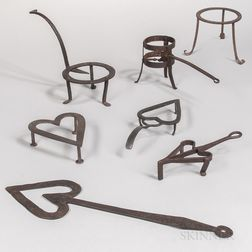 Six Wrought Iron Trivets and a Heart-shaped Tool