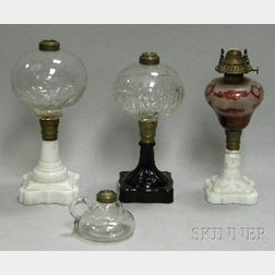Three Colorless Molded Glass Oil Lamps with Colored Pressed Glass Bases and a Colorless Glass Hand Lamp.