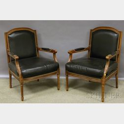 Pair of Chateau DAx Louis XVI-style Black Leather Upholstered Carved Walnut Fauteuil.