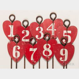 Set of Nine Red-painted Tin and Iron Heart-shaped Golf Hole Markers