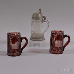 One Colorless and Two Etched Cranberry Glass Steins
