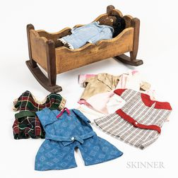 Black Cloth Doll, Group of Handmade Doll Clothes, and a Carved Doll Cradle