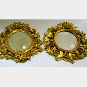 Matched Pair of Continental Floral Carved Giltwood Oval Mirrors.