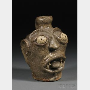 Sold for: $56,288 - Stoneware Face Jug