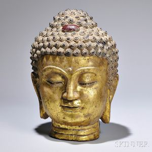 Cast Iron Buddha Head, China, the gilt face with downcast eyes and smiling lips, ht. 15 1/8 in.
