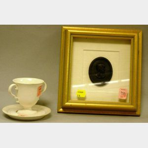 Wedgwood & Bentley Basalt Waller Medallion and a White Stoneware Two-Handled Cup and Saucer.
