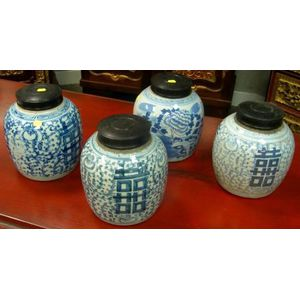 Four Chinese Blue and White Decorated Porcelain Jars with Wood Covers.