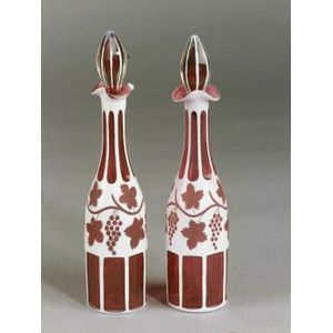 Near Pair of Bohemian Cranberry, Clear Cased, and White Flashed Cut Glass Decanters