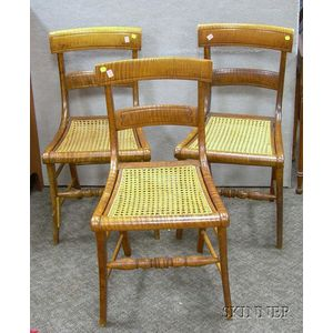 Three Classical Carved Tiger Maple Side Chairs with Caned Seats.