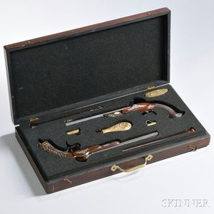 Cased Set of French Target Pistols, c. mid-19th century, a dueling pistol with ornate foliate carvings on the stock, marked on the lock