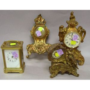 Three French-style Gilt Cast Metal Table Clocks and a Waterbury Clock Co. French-style Brass and Glass Carriage Clock.