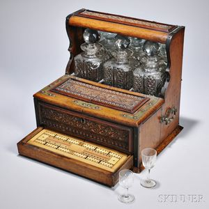 Carved Oak Liquor Set, England, late 19th century, comprising three square cut glass decanters with stoppers, above two hinged lids ope
