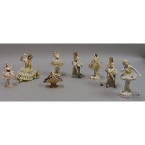 Seven Assorted Crinoline Figurines and a Porcelain Fruit Basket
